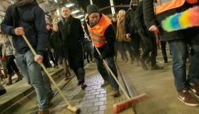 Counter-demonstrators symbolically sweep away racism.