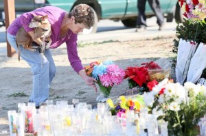 Woman leaves flowers for the victims in the San Bernardino, California attacks. Photo credit to International Business Times